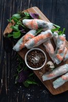Rice paper rolls on a wooden serving board with a peanut hoisin dipping sauce in a small dish