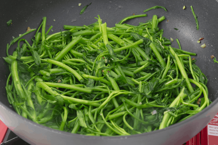 Cooked water spinach in a wok
