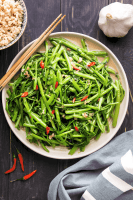 Water spinach stir fried in a plate with chopsticks to the side