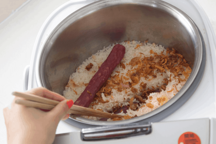 Chopsticks pushing Chinese sausages into rice in a rice cooker