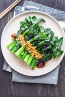 Chinese broccoli on a plate with oyster sauce and minced garlic