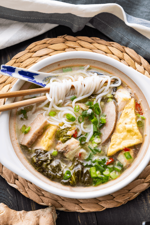Chinese fish soup with noodles in a bowl with chopsticks