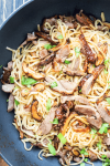 Roast duck and mushrooms in a wok with noodles