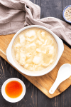 Fish maw soup in a bowl with vinegar and a spoon