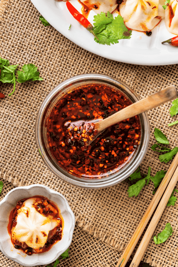 Chilli oil in a glass container with a spoon and dumplings on the side