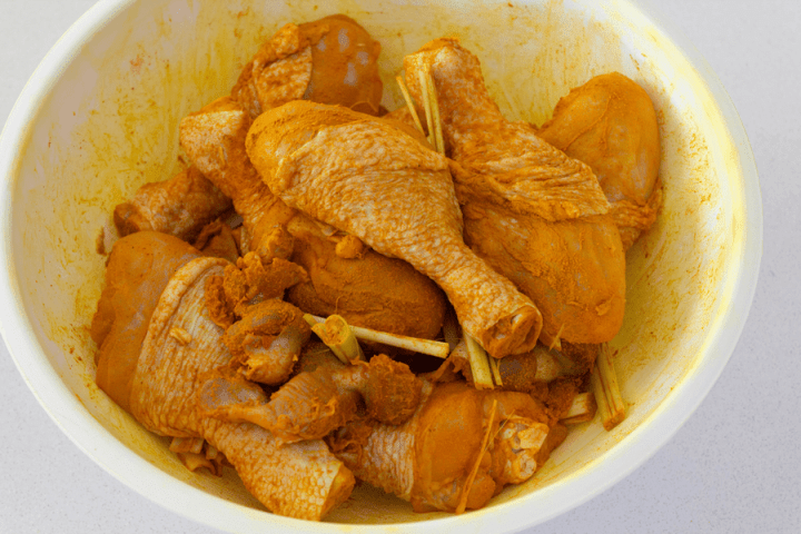 Chicken drumsticks marinated with tumeric powder in a bowl with lemongrass