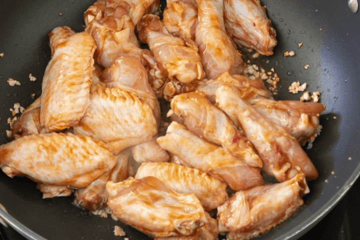 Chicken wings and garlic in a wok