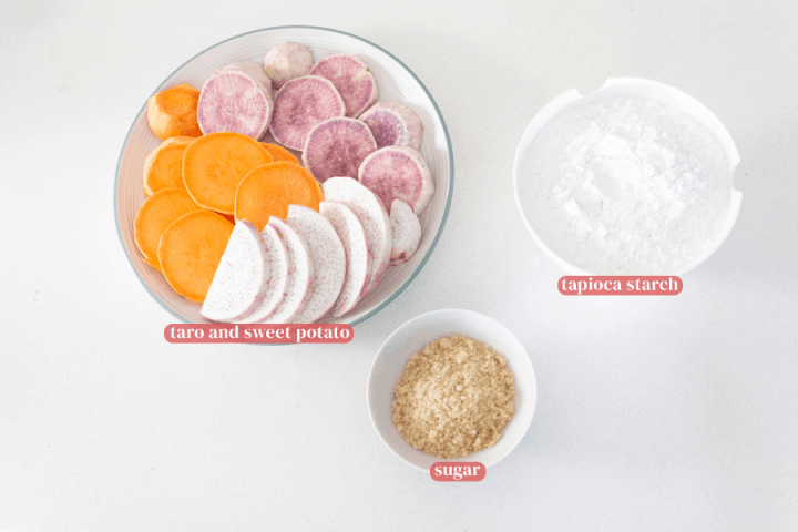 Taro and sweet potato slices on a plate next side a bowl of tapioca starch and a bowl of sugar