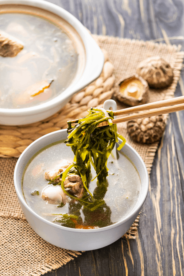 Watercress held up by chopsticks in a bowl with soup