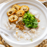 Fish congee in a bowl with spring onions, fried garlic, fried crullers and a spoon