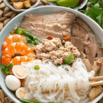 Prawns, sliced pork, mince, rice noodles and quail eggs in a bowl with chopsticks