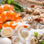 Rice noodles with quail eggs, prawns, pork mince, pork slices and spring onions in a bowl