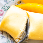 Mango pancake cut in half with a fork on a plate with mango pieces