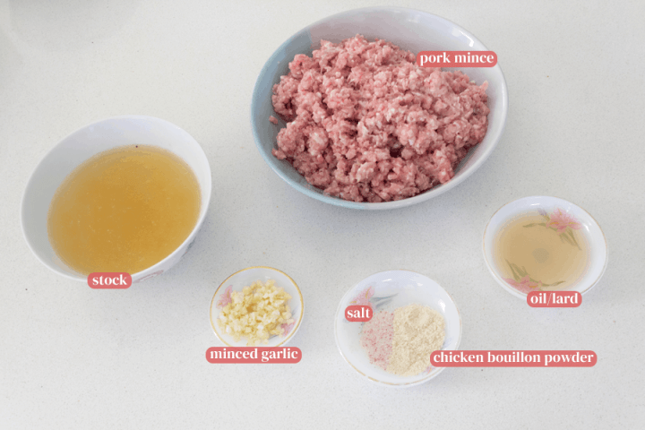 Stock and pork mince in bowls along with minced garlic, salt, chicken bouillon powder and oil in dishes