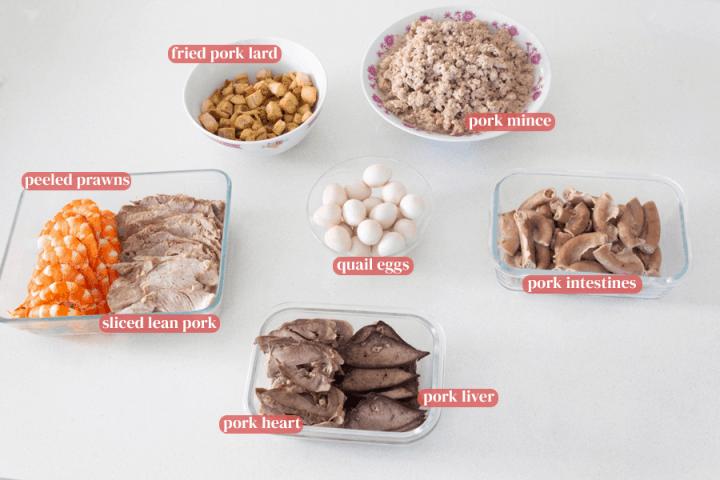 Fried pork lard, pork mince and quail eggs in a bowl along with peeled prawns, sliced pork, pork intestines, pork heart and pork liver in dishes