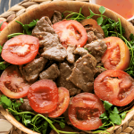 Beef and tomato slices in a bowl with watercress