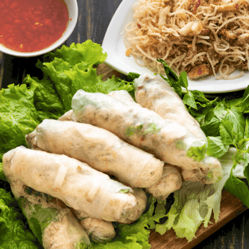 Rice paper rolls on lettuce with a plate of bi