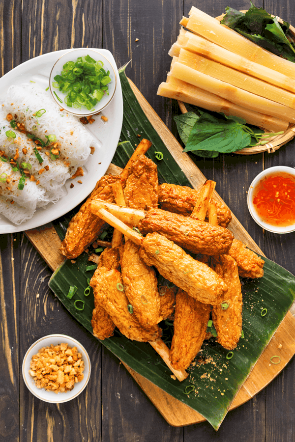 Sugar cane wrapped in fried prawn paste on banana leaf and a wooden board with a plate of woven rice noodles, sugar cane and crushed peanuts