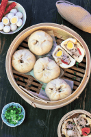 Banh Bao in a steamer with one halved surrounded by quail eggs and chopped spring onions