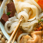 Banh Canh Cua in a bowl with chopsticks twirling the noodles
