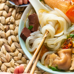 Tapioca noodles wrapped around chopsticks in a spoon in a bowl of Banh Canh Cua