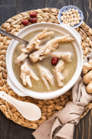 Chicken feet soup in a bowl with a spoon, red dates and ginger to the side