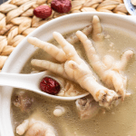 Chicken feet soup in a bowl with a spoon scooping chicken feet