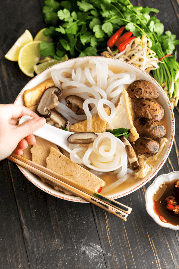 Banh canh chay in a bowl with a hand holding a spoon and chopsticks