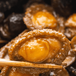 Braised Abalone with Mushrooms held up by chopsticks