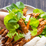 Nem Nướng in a lettuce wrap held by a hand