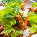 Nem Nướng on a plate of salad next to a dish of fish sauce