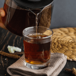 Chinese Herbal Tea in a glass cup with a teapot pouring tea into it