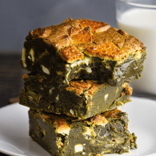 Matcha Brownies stacked on a plate with one bitten intoin front of a glass of milk