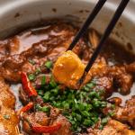 Cá Kho Tộ on a pot with chopsticks holding fish up