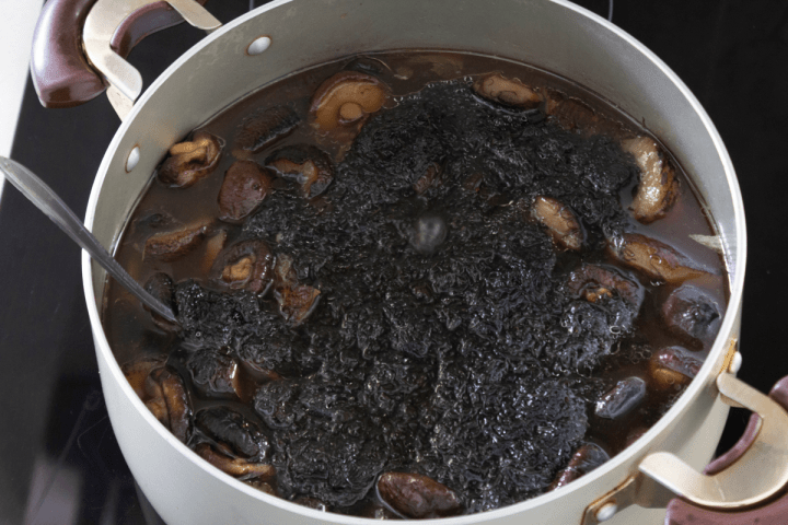Black moss over mushrooms and sea cucumber in a pot