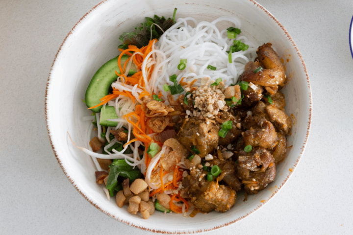 Grilled pork, noodles and salad in a bowl garnished with crushed peanuts