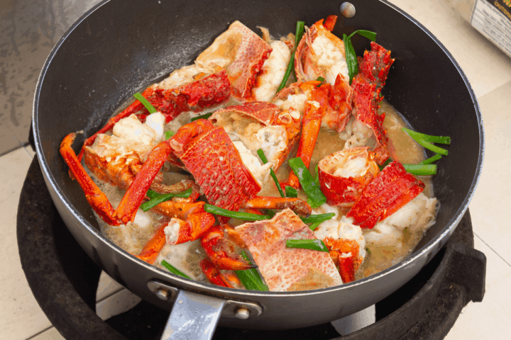 Lobster and scallions in a wok with sauce.