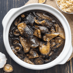 Braised sea cucumber in a pot surrounded by a bowl of rice, a garlic bulb and mushrooms