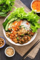 Bun Thit Nuong in a bowl surrounded by chopsticks, salad and dishes of pork fat and crushed peanuts