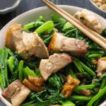 Pork and greens stir fry in a bowl with chopsticks