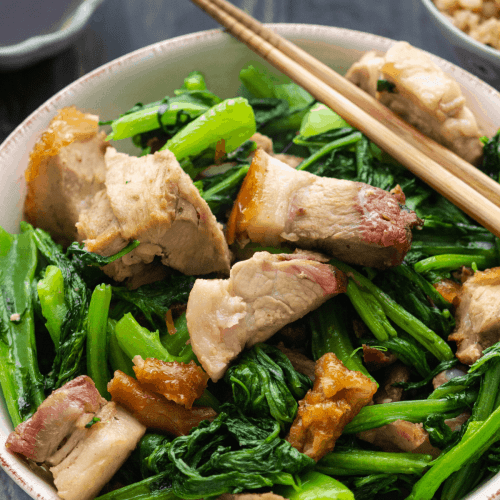 Pork and greens stir fry in a bowl with chopsticks