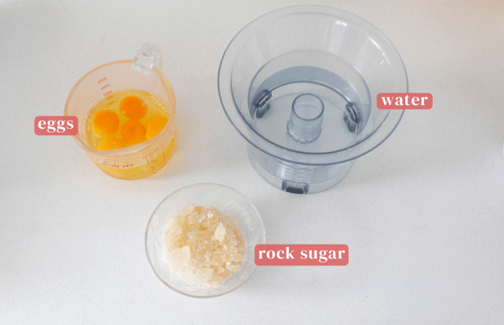 Eggs in a measuring cup along with a measuring container of water and rock sugar in a bowl