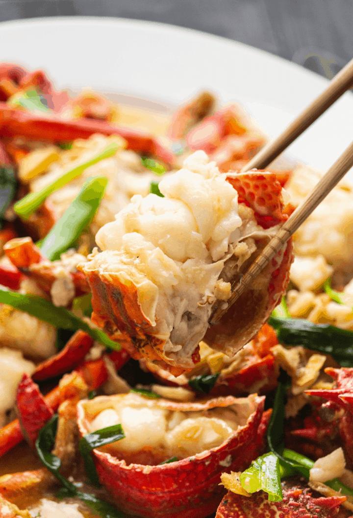 Ginger Scallion Lobster held up by chopsticks.