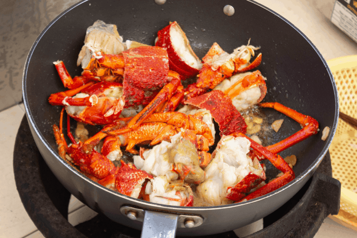 Cooked lobster pieces in a wok.