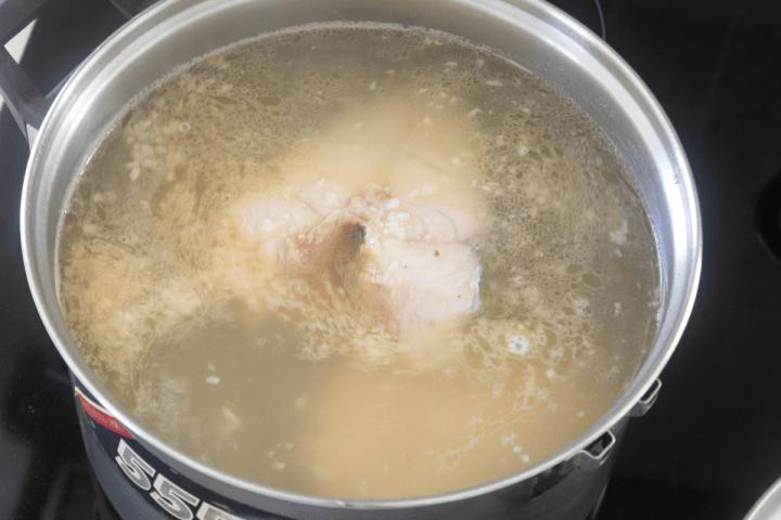 Fish steaks in a pot of seasoned water.