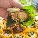 Bánh Khọt on a plate with a hand holding one up wrapped with salad.