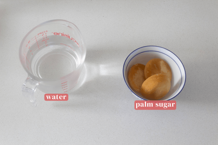 Water in a measuring cup along with palm sugar in a bowl.