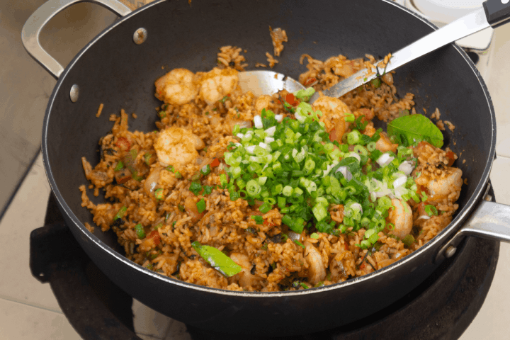 Chopped spring onions on Tom Yum Fried Rice in a wok with a metal spatula in it.