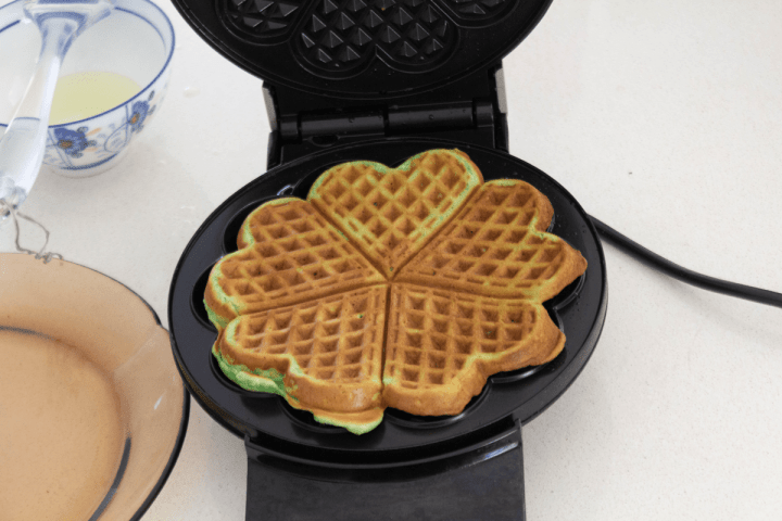 A cooked pandan waffle in a waffle maker.