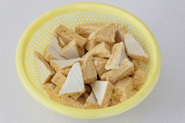 Tofu triangles halved in a colander.